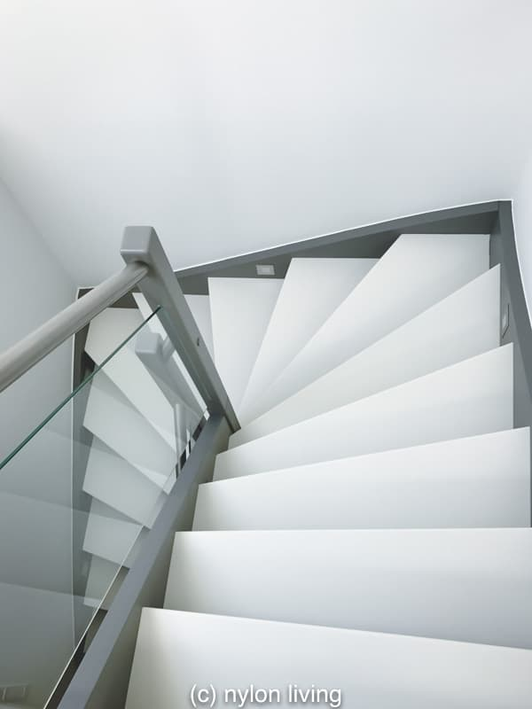 A White Corian Staircase Warmed Up With Wood And Glass