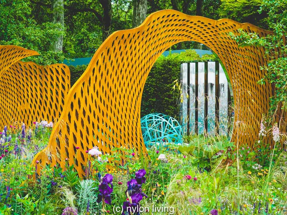 You can see the bench peeking through the metal garden ornaments #gardenideas #gardenart #gardensculpture #gardendecor #gardeninspiration #gardendesign #moderngardens #metalgardenart #chelseaflowershow #sculpture #RHSchelsea #gardening #bronze #outdoordesignUK