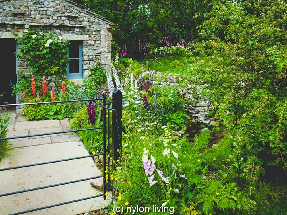 A stone bridge leads over the stream to the stone cottage #RHSchelsea #gardeninspiration #gardendesign #ChelseaflowerShow #UKtravel #Yorkshire #England #NorthYorkshire #statelyhome #countryhouse #NationalTrust #UKdaysout #garden_styles #gardenideas #Englishgarden #Englishcountryside #EnglishCountryGarden #Englishcountryhouse #gardens