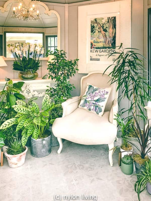 Garden summer house ideas include bringing plants inside to create a cozy hideaway.