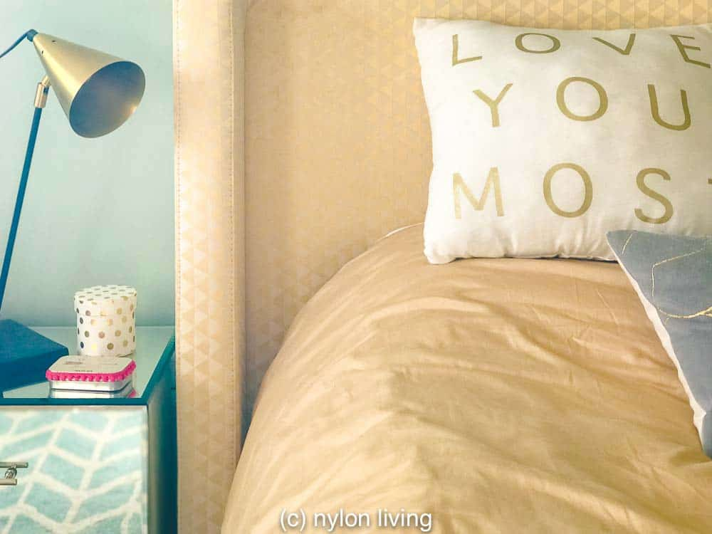 A mirrored bedside table and gold bedding adds to the sparkle factor.