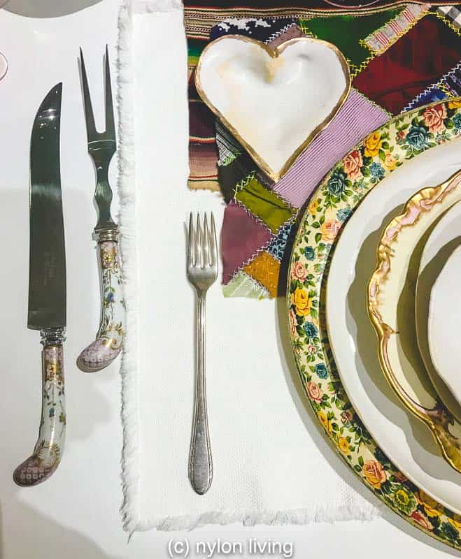 Vintage silverware and plates make up a boho table setting