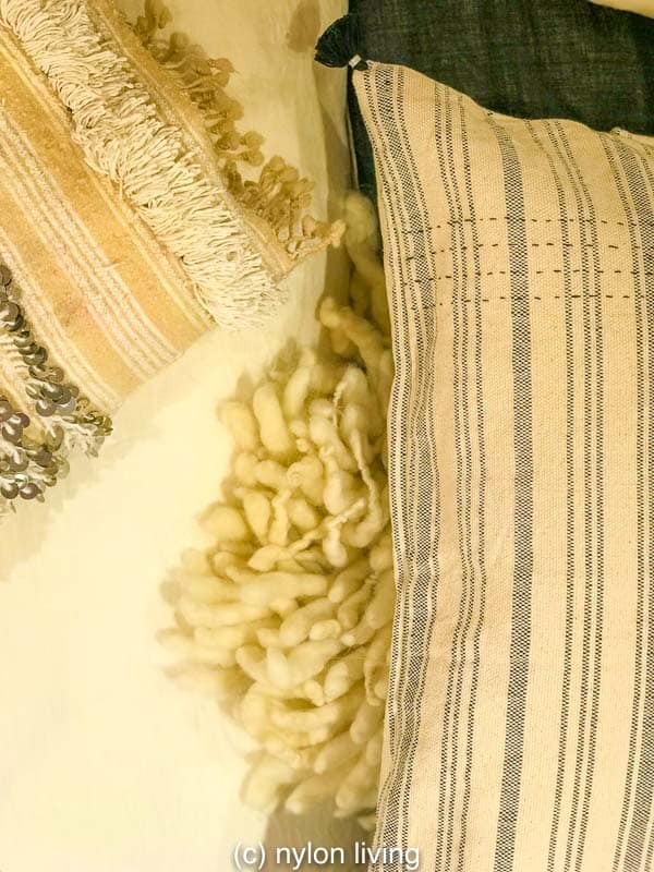 A Moroccan wedding blanket adds an artisanal chic and texture to a neutral color scheme