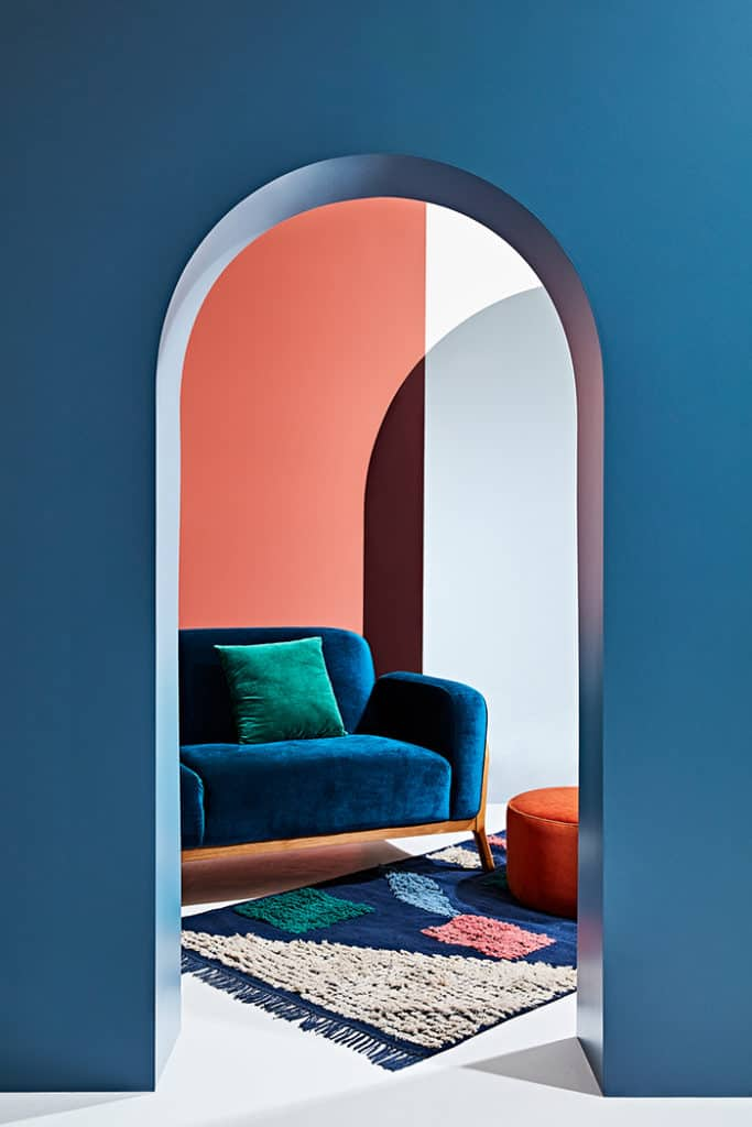 Coral and blue combine well in this image of a blue velvet sofa against a coral wall - definitely not a winter look. image credit: Arro Home and We Are Scout