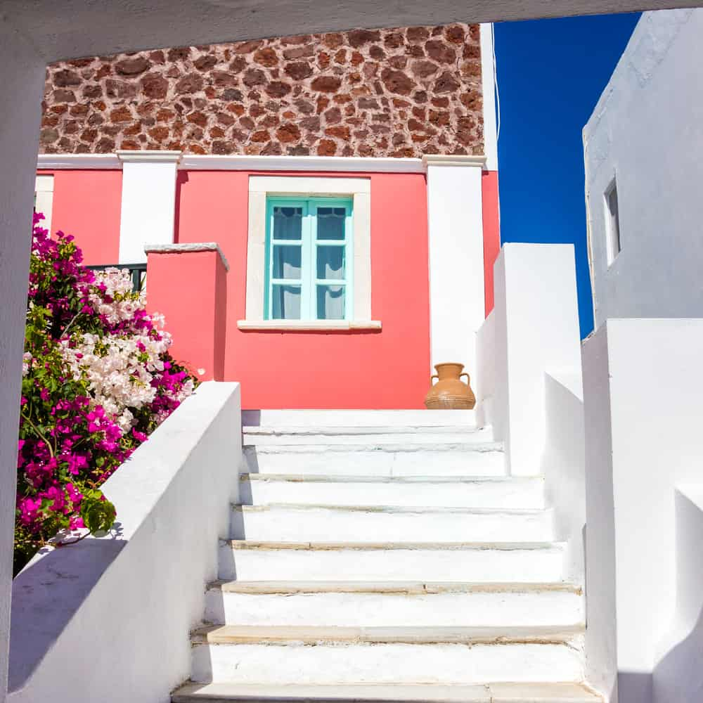 coral and white really pop against the blue sky on a house in Santorini Greece