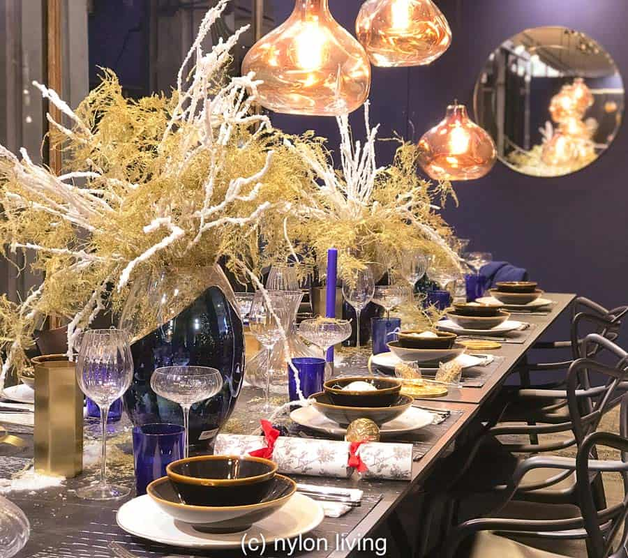 Beautiful Christmas table settings on the table and a cluster of Tom Dixon lamps above