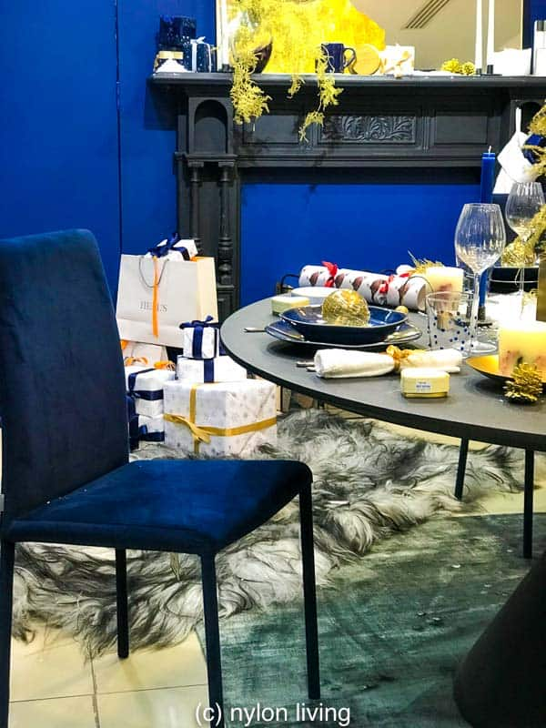 Navy blue Christmas decorations, a navy table setting and deep blue walls keep the theme consistent