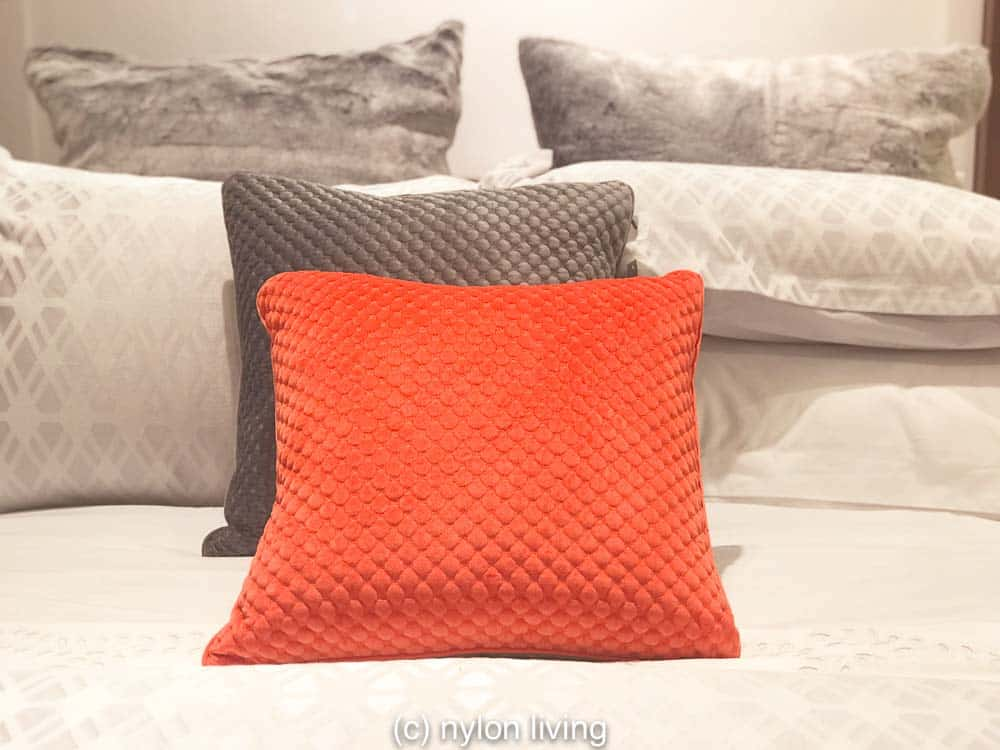 One well placed decorative pillow creates this coral and grey color scheme