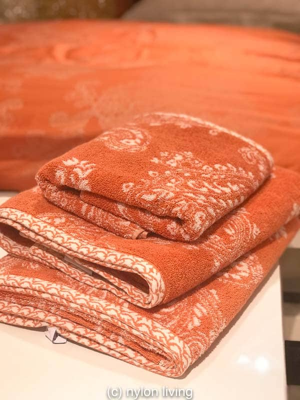 A set of coral coloured bath towels
