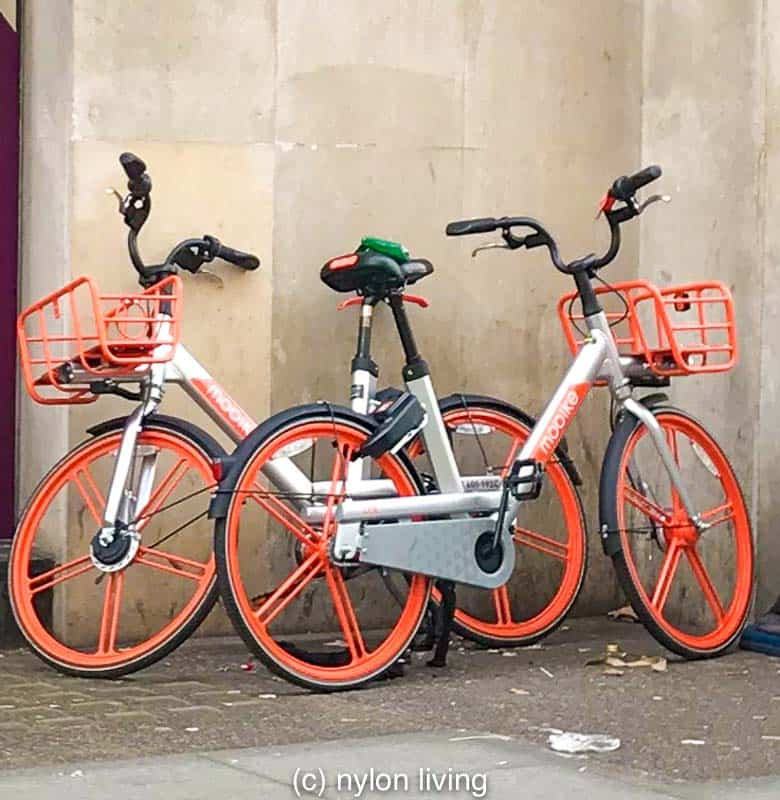 Rental bikes on the streets of London in a trendy shade of coral