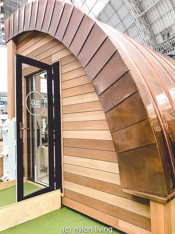 A prefab backyard studio with a gleaming copper roof.