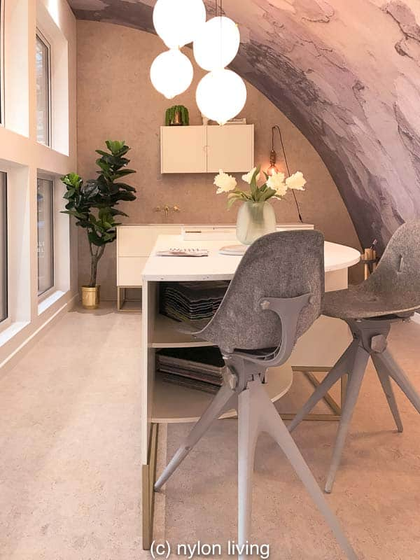 The large work table in the middle of this small garden office allows multiple people to work together.