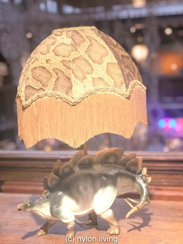 No need to be stuffy - how about a non traditional animal base with lampshade fringe like this dinosaur?