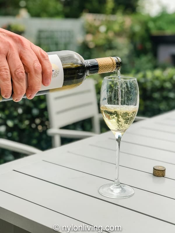 pouring white wine into glass in garden