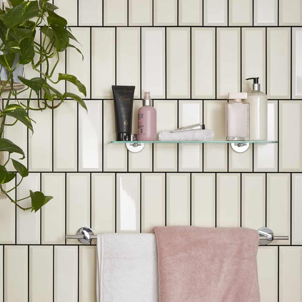black grout and champagne coloured tiles in a bathroom