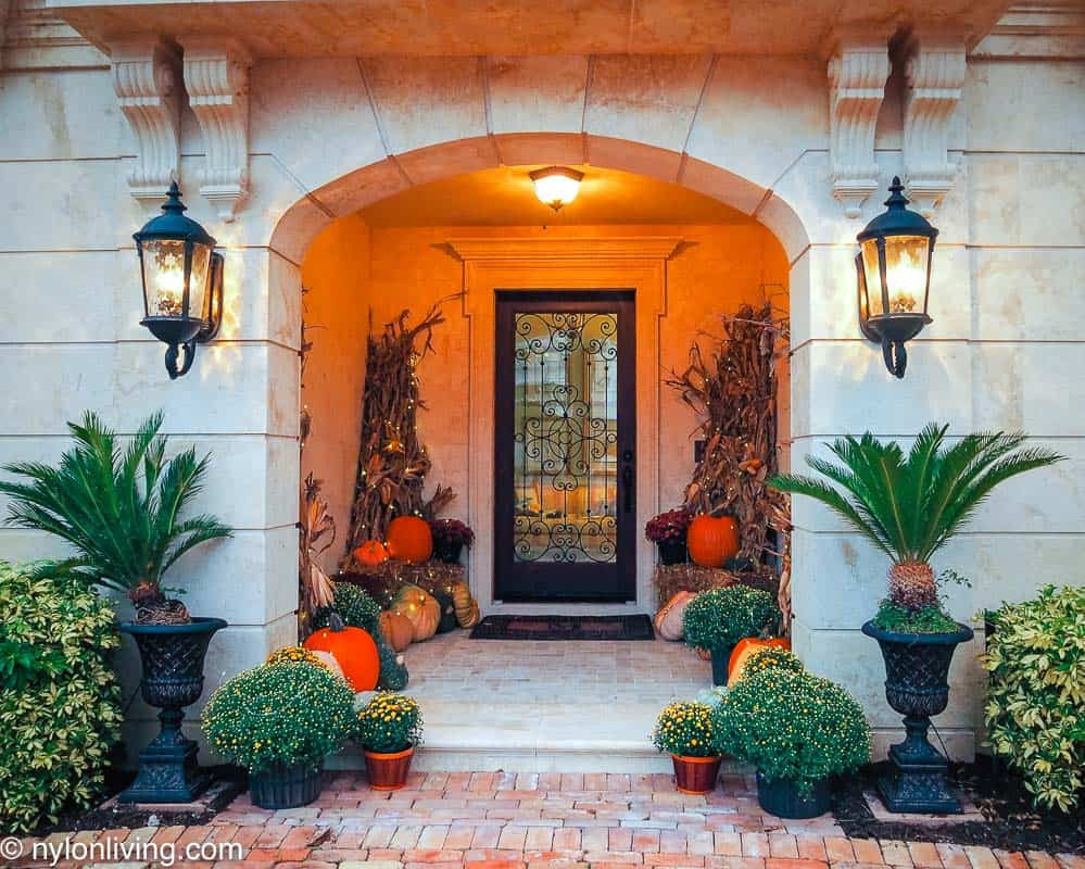 a fall entryway with lights and pumpkins and corn