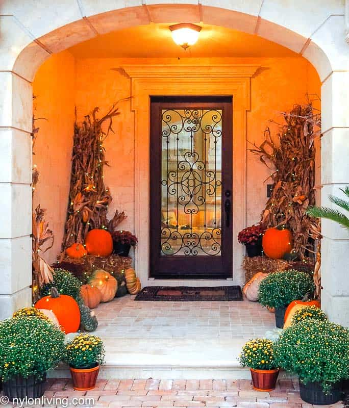 a fall entryway tableau with pumpkins
