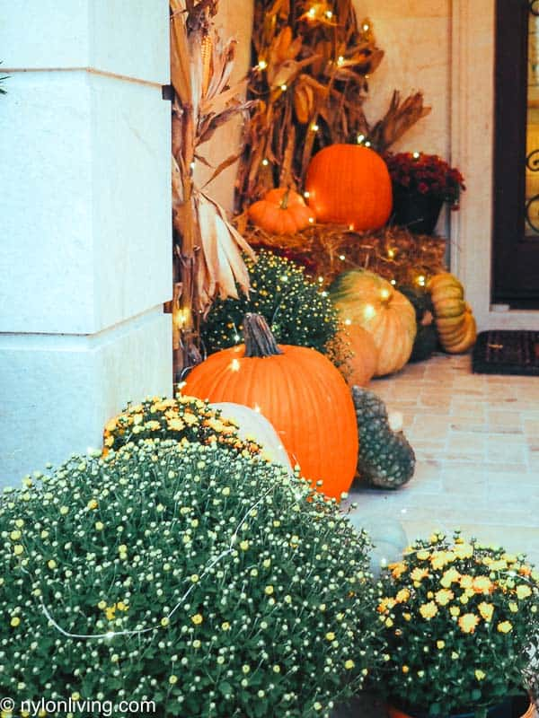 a fall entryway with lights and pumpkins