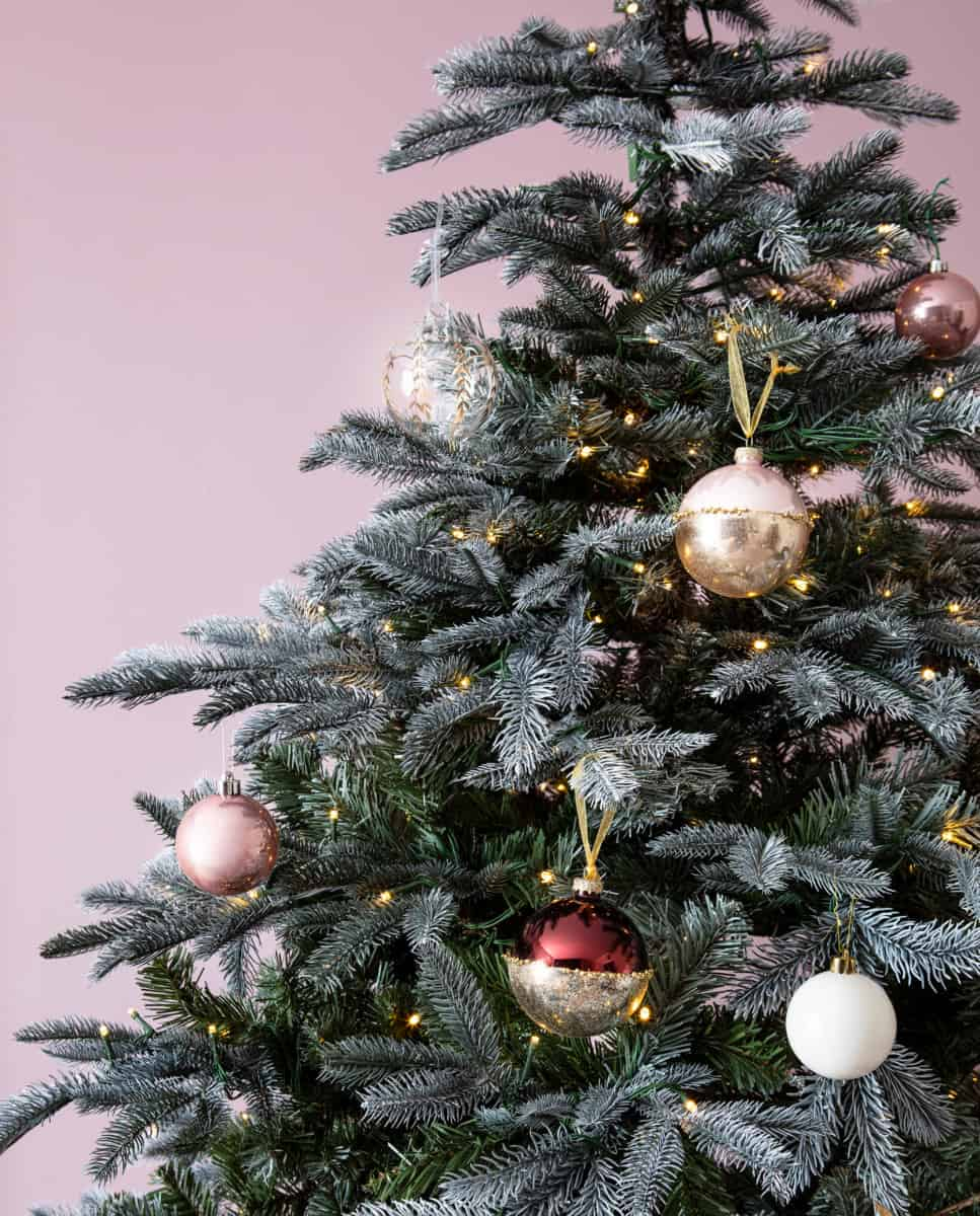 pink christmas ornaments on a green christmas tree