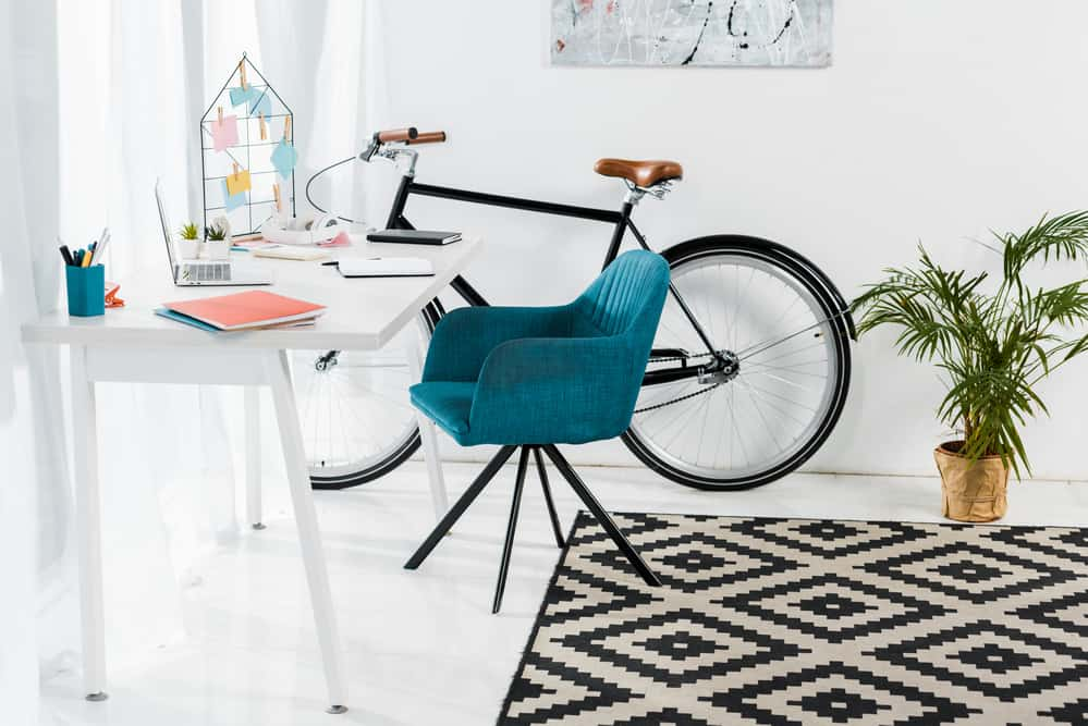 Home workspace setup with white desk, blue chair and bicycle