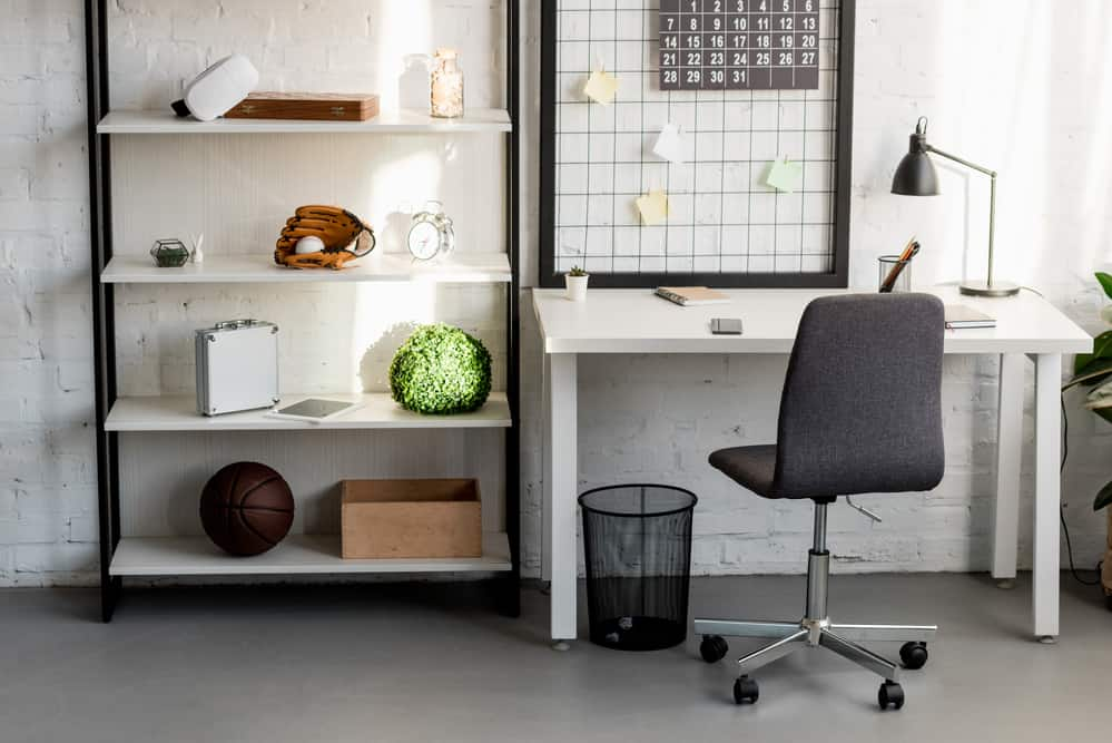 work from home space with white desk, white shelves and grey rolling office chair